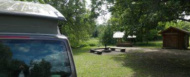 Bulli mit aufgestelltem Hochdach auf Campingsite mit Feuerstelle und Wasserzugang Somoo NP